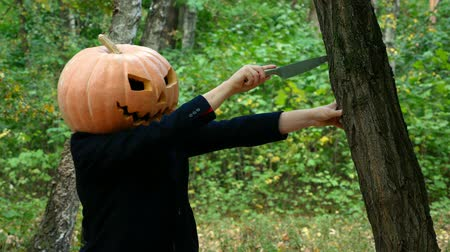 grão : A man with a pumpkin on his head. He pulls out a knife from a tree. Halloween