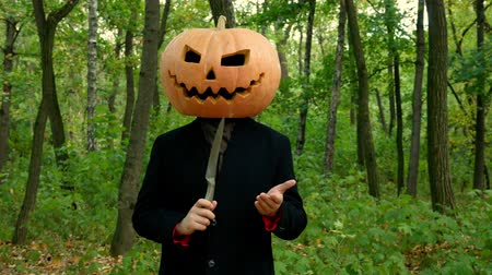 острый : Halloween pumpkin head faces in the autumn forest, play with a knife in the hands