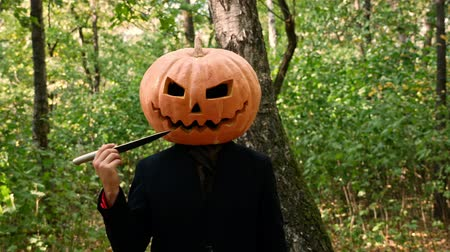 острый : Jack Pumpkinhead stands in the forest, fumbling with a knife near his face. The guy puts a real pumpkin on his head. Halloween concept Стоковые видеозаписи