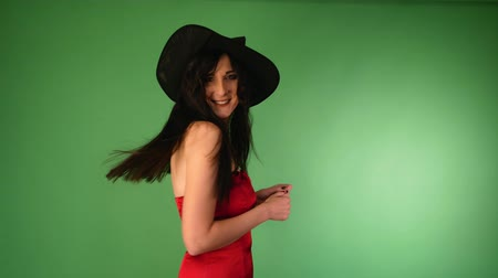 witchcraft : young beautiful woman in a red dress and a witchs hat, laughing loudly and looking at the camera. green background. halloween concept. 4k