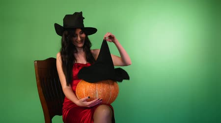 feiticeiro : young beautiful woman in a red dress and a witches hat, sits on a chair holding a pumpkin in her hands and puts a witch hat on her. Green background. Halloween concept.4k Stock Footage