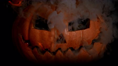 diabeł : Scary carved halloween pumpkin in the burning fire of hell flame. Fire from the eyes and smoke from the mouth full of teeth