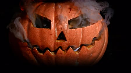 carving : A terrible Halloween pumpkin burns with hellfire. Smoke from the eyes, fire from the mouth.