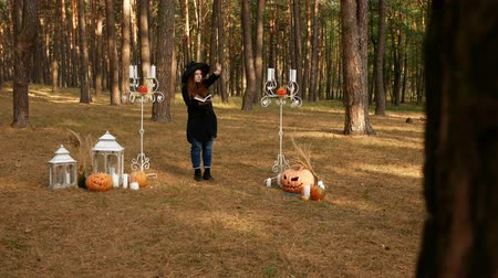 ужасный : Red-haired girl in a witchs hat and jeans, in the middle of a forest surrounded by terrible pumpkins and candlelight. He reads spells.