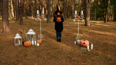 korkunç : Redhead girl in a witchs hat, in the middle of the forest, surrounded by terrible pumpkins and candles Stok Video