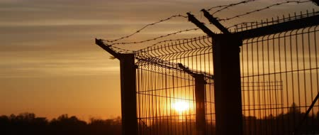 farpado : Prison barbed wire fence at sunset. Jet airplane cutting across the sky. Stock Footage