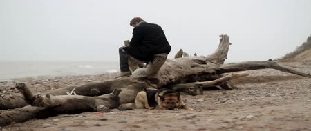 almanca : Lonely man sitting on the beach, with his German Shepherd dog. Stok Video