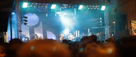 színpad : People in a rock and roll concert. Performers up on stage. Mounted camera moving across the screen. Stock mozgókép