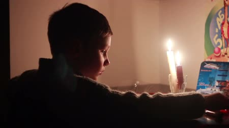 yazarak : Boy draws a picture by candlelight. Turn off the electricity, global cataclysm Stok Video