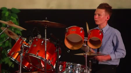playing band : Boy playing drum set in the room on the stage Stock Footage