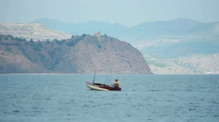 fenerbalığı : Fisherman on the boat with fishing rods floats on the sea