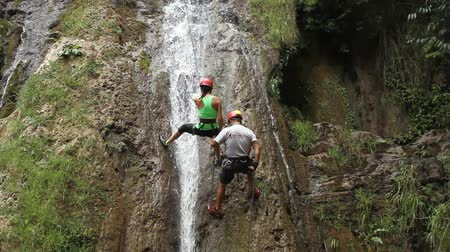 редакционный : HD video of two person, a man and a woman, doing rock climbing on a waterfall (going down). Santa Catarina, Puebla
