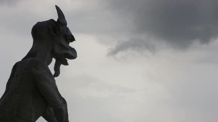 grotesque : Sculpture of Notre Dame against running clouds