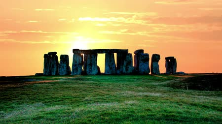 arqueológico : Sunset over the stones of Stonehenge, the sun is moving rapidly across the sky, summer evening Stock Footage