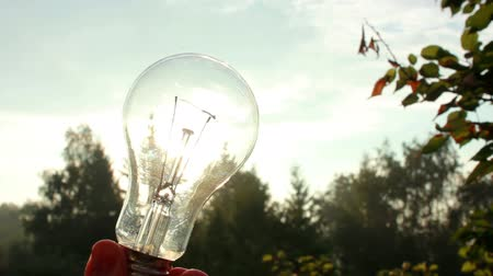 estame : Sun rays are going through the light bulb in a hand. Shallow dof, highly energy concept footage.