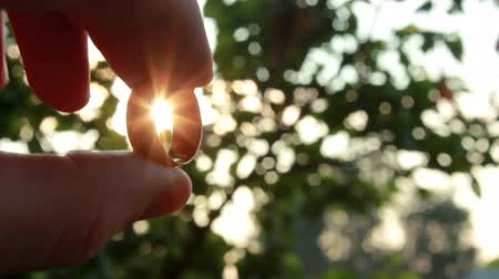 casado : Sun rays are going through the Gold Ring in a hand Stock Footage