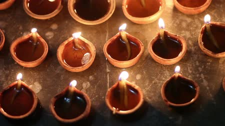 dussehra : traditional mud lamps being lit on indian festival,