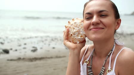 оболочка : Young happy woman with seashell sitting on the beach  Стоковые видеозаписи