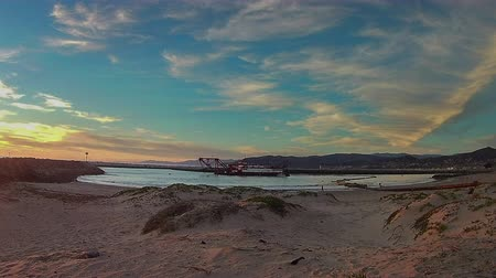 Time lapse of Ventura harbor cove dredging working through sunset. Стоковые видеозаписи