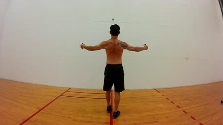 Shirtless Japanese middle age man resistance band exercise rear deltoid from rear view.