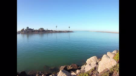 Time lapse of Ventura Harbor mouth variety of vessels passing through.