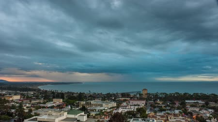 Time lapse of ominous rain clouds moving over panoramic city of Ventura at dawn.