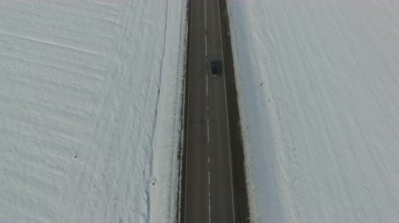Aerial shot of cars driving on a road on winter sunny day. Drone moves down. Stock mozgókép