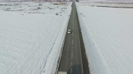 geada : Aerial shot of cars and trucks driving on a road on winter sunny day. Drone moves along road. Stock Footage