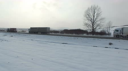 lanscape : Aerial shot of truck driving winter road in snowy field. Drone shooting.