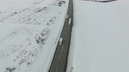 lanscape : Aerial shot of vehicle and bus driving winter road in snowy field. Drone shooting.