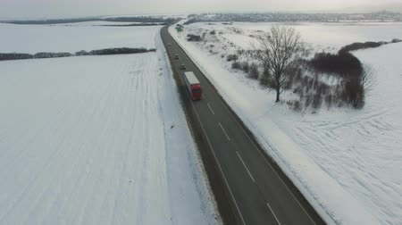 lanscape : Aerial shot of truck and cars driving winter road in snowy field. Drone shoot.