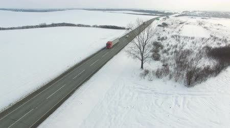 Aerial shot of truck and cars driving winter road in snowy field. Drone shoot.