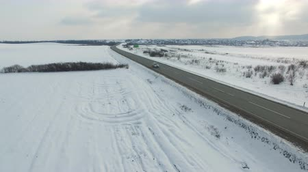 Aerial shot of cars and trucks driving on a road on winter cloudy day. Drone moves along road. Stock mozgókép