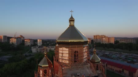 Aerial view of constructed church in Lviv, Ukraine. Aerial shot flying up along church. Spring sunset.