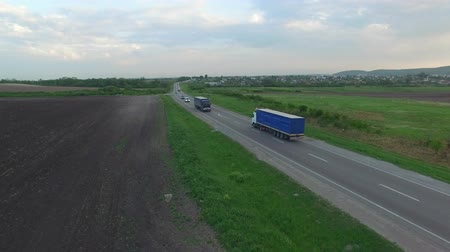 Aerial shot of truck driving a road benween fields. Sunset time. Spring season.