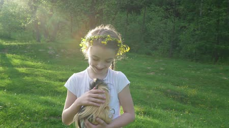 gine : Child blond girl holding her guinea pig pet animal. Handheld smooth footage outside. Summertime. Slow motion.