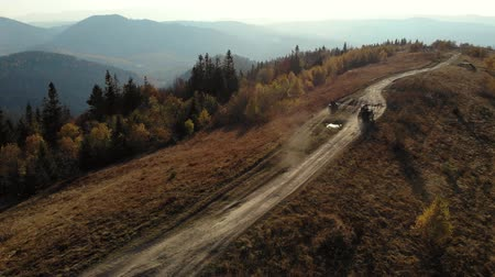 Quad bikes and SUV going on mountaint road. Sunny Autumn daytime. Aerial view. 4K