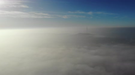 Flying over clouds. Video shot by drone in early morning. Smog above city. Look at the city television tower. Real time footage. 4K