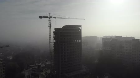 ремонт : Birds eye view on tower crane in fog standing next to residential building. Flying over the construction site. Drone real time footage. 4K Стоковые видеозаписи