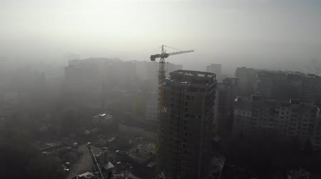reparaciones : Birds eye view on tower crane in fog standing next to residential building. Flying over the construction site. Drone real time footage. 4K Archivo de Video