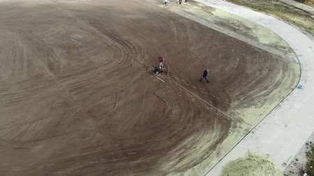 Aerial shot of workers assembling irrigation system on school football stadium. 4K