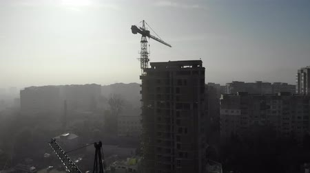 Birds eye view on tower crane in fog standing next to residential building. Flying over the construction site. Drone real time footage. 4K Stock mozgókép