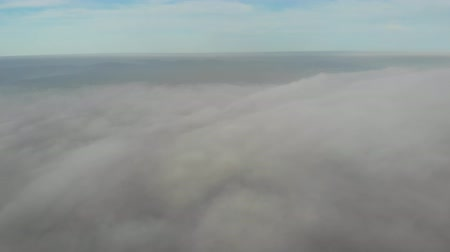 Flying over clouds. Video shot by drone in early morning. Smog above city. Look at the church dome through clouds . Real time footage. 4K Stock mozgókép
