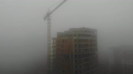 Birds eye view on tower crane in fog standing next to residential building. Flying over the construction site. Drone real time footage. 4K Stockvideo