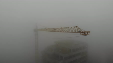 Birds eye view on tower crane boom in fog standing next to residential building. Flying over the construction site. Drone real time footage. 4K