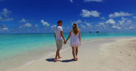 kumlu : Maldives white sandy beach  young couple walking together in love on sunny tropical paradise island with aqua blue sky sea water ocean 4k Stok Video