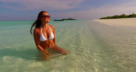 opalenizna : Maldives white sandy beach young beautiful lady sunbathing alone on sandbar on sunny tropical paradise island with aqua blue sky sea water ocean 4k