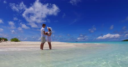 öneri : Maldives white sandy beach 2 people young couple man woman proposal engagement wedding marriage on sunny tropical paradise island with aqua blue sky sea water ocean 4k Stok Video