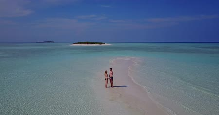 magas, szög, kilátás : Aerial flying drone view of Maldives white sandy beach 2 people young couple man woman romantic love on sunny tropical paradise island with aqua blue sky sea water ocean 4k Stock mozgókép