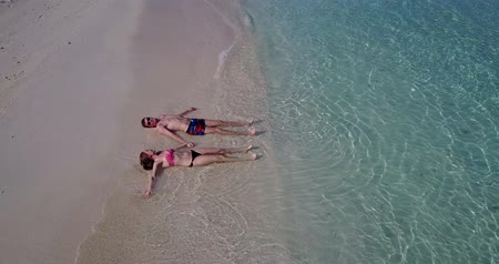 z lotu ptaka : Aerial flying drone view of Maldives white sandy beach 2 people young couple man woman romantic love on sunny tropical paradise island with aqua blue sky sea water ocean 4k Wideo